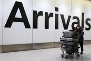 Una pasajera llega con máscara al aeropuerto de Heathrow (Londres)