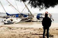 Un hombre mira tres embarcaciones varadas en Pollença (Mallorca) por el oleaje.
