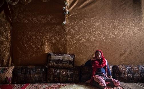 Una joven jornalera de 13 años descansa en su tienda un día de lluvia. Comenzó a trabajar a los 11. Vive y trabaja con su abuela, porque sus padres murieron en Siria a causa de la guerra.
