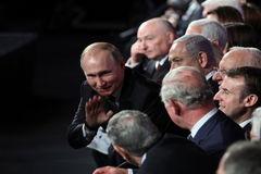 El presidente ruso Vladimir Putin saluda a Carlos de Inglaterrra, al lado de Emmanuel Macron, durante la ceremonia en Jerusalén.