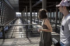 Dos pasajeros atraviesan el paso superior de los andenes del AVE en la estación de Atocha, en Madrid.