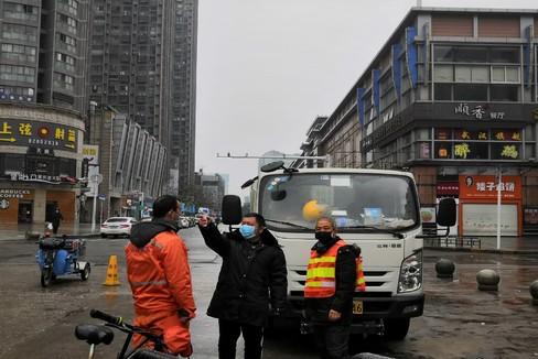 Chou toma la temperatura a los viandantes con los que se cruza en Wuhan.