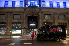 Un camión de Netflix y actores vestidos como los de la serie 'La casa de papel', ante la sede de Telefónica en Gran Vía.