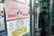 Cartel con precauciones por el coronavirus en una estación de Corea.