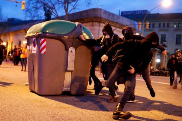Manifestantes independentistas golpean un contenedor en el exterior...