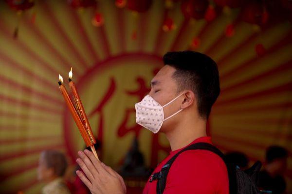 Un hombre reza en un templo chino en Tailandia