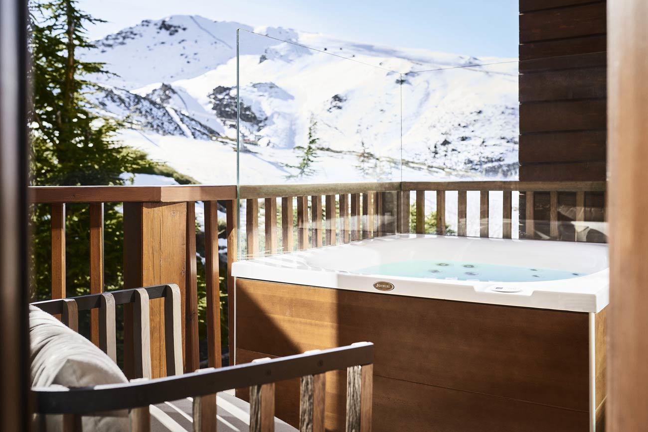 """A más de 2.000 metros, <a href=""""https://www.ellodge.com"""" target=""""_blank"""">El Lodge Ski & Spa</a> se ha convertido en toda una referencia como el hotel <em>boutique </em>más exclusivo de Sierra Nevada (Granada). Entre sus opciones <em>après-ski</em> destacan actividades tan interesesantes como visita al obrador  La Flor de Vainilla para aprender Ia técnica de la <em>repostectura  </em>(recrear elementos arquitectónicos de la Alhambra o el pico de Sierra Nevada utilizando ingredientes ecológicos); sobrevolar Granada en globo; probar el caviar de Ríofrío en el Huerto de Juan Ranas; visitar la Alhambra y los Palacios Nazaríes de noche de la mano de un guía local; y por supuesto, disfrutar del spa y de las habitaciones con vistas del hotel. Desde <strong>350 euros</strong>/noche."""