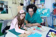 María, en el aula donde juega, aprende y recibe tratamiento. E.M.