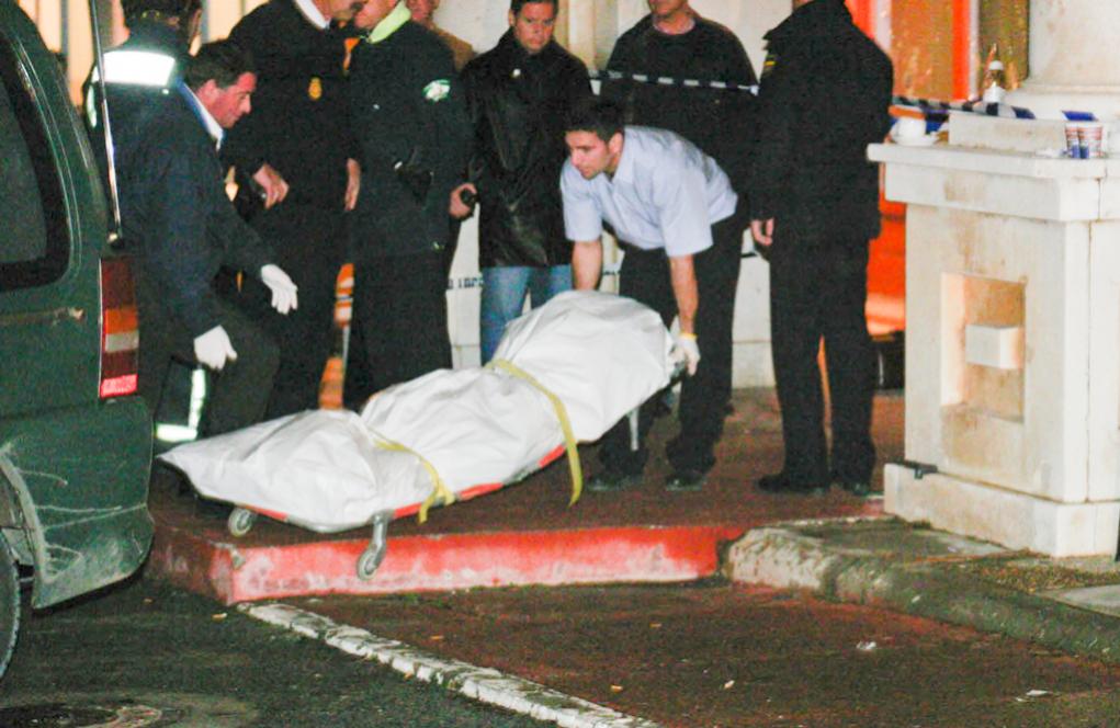 Operarios de la funeraria introducen el cuerpo del peluquero asesinado...