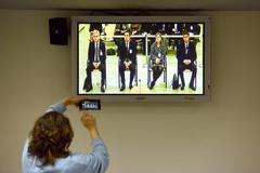 Una periodista fotografía la imagen de los cuatro acusados en el juicio que se sigue en la Audiencia Nacional contra la ex cúpula de los Mossos por el 'procés'.