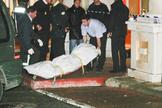 Operarios de la funeraria introducen el cuerpo del peluquero asesinado en el furgón mortuorio.