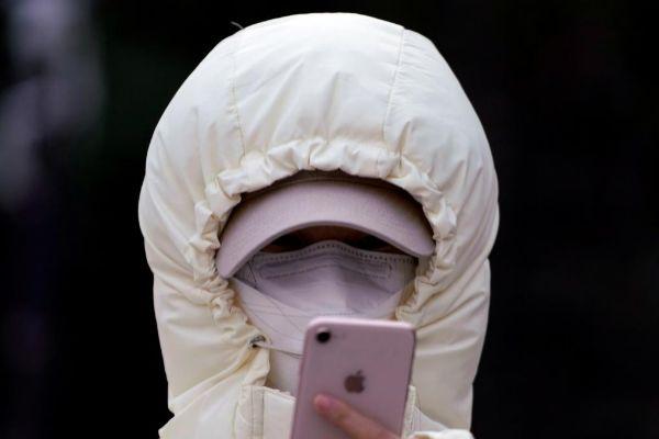 Una mujer mira el móvil con la mascarilla de protección contra el contagio