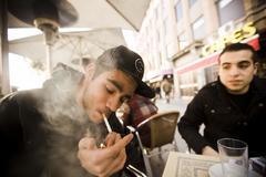Un joven enciende un cigarrillo en una terraza de Madrid.