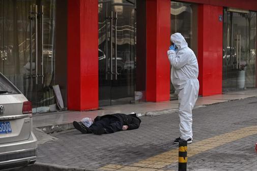 Un hombre yace muerto en una calle de Wuhan, en China.