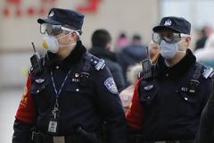 Dos policías chinos con mascarillas y gafas protectoras en Pekín.