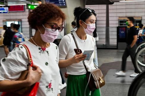 Varias personas se protegen con una mascarilla en una estación de Bangkok.