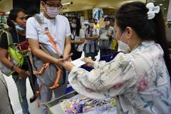 La gente hace cola en una tienda de Manila donde se reparten mascarillas gratuitamente.