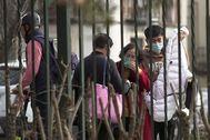 Un grupo de turistas se protege con mascarillas cuando pasea por las calles de Sevilla.