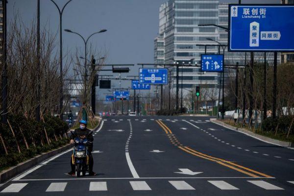 Un motorista circula por una avenida vacía en Hangzhou | Noel Celis AFP