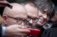 Carles Puigdemont escucha a Gonzalo Boye (en primer término) atender a la prensa en Bruselas.