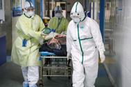 Sanitarios llevan a un paciente infectado con coronavirus a aislamiento en el hospital de Wuhan, origen de la epidemia en China.