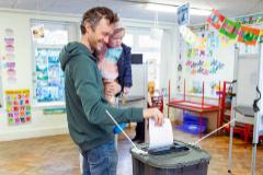 Un votante deposita su papeleta con su hija en brazos en Cork.