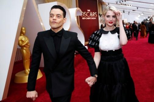 Lucy Boynton, junto a su pareja Rami Malek, en los Oscar, con los labios rojos.