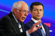 Pete Buttigieg (Der.) escucha a Bernie Sanders (Izq.) en un debate en Iowa.