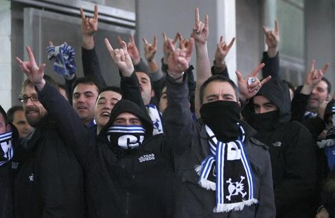 Aficionados radicales realizan gestos obscenos en un estadio.
