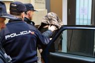 Agentes de la Policía trasladan a uno de los detenidos a los juzgados.