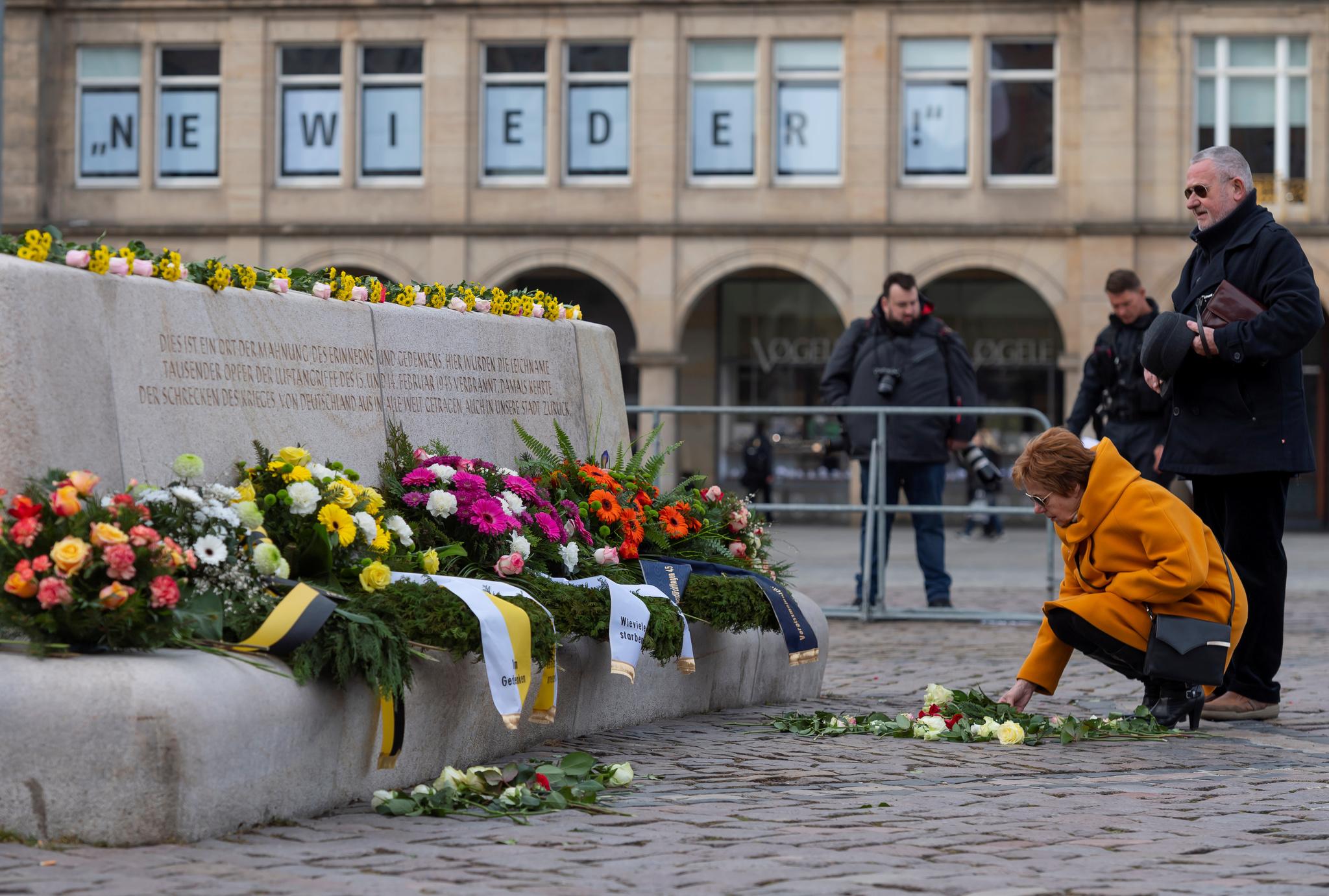 Una mujer deposita flores en el memorial por las víctimas del bombardeo.