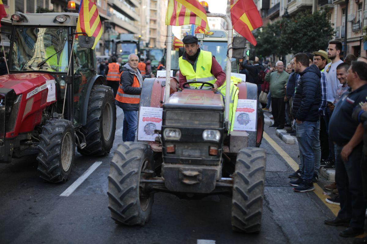 Un agriculturor conduce un tractor por las calles de Valencia en protesta por la crisis del campo.