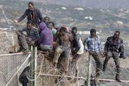 Inmigrantes de origen subsahariano permanecen encaramados en la parte alta de la valla de Melilla en 2014.