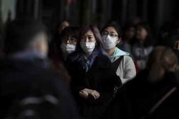 Turistas asiáticos con mascarilla en el centro de París.