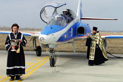 Dos religiosos bendicen un avión de combate.