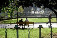 Dos hombres descansan en un banco en el céntrico parque de Los Hermanos