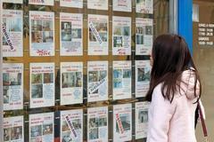 Una mujer observa los precios de viviendas en una agencia inmobiliaria