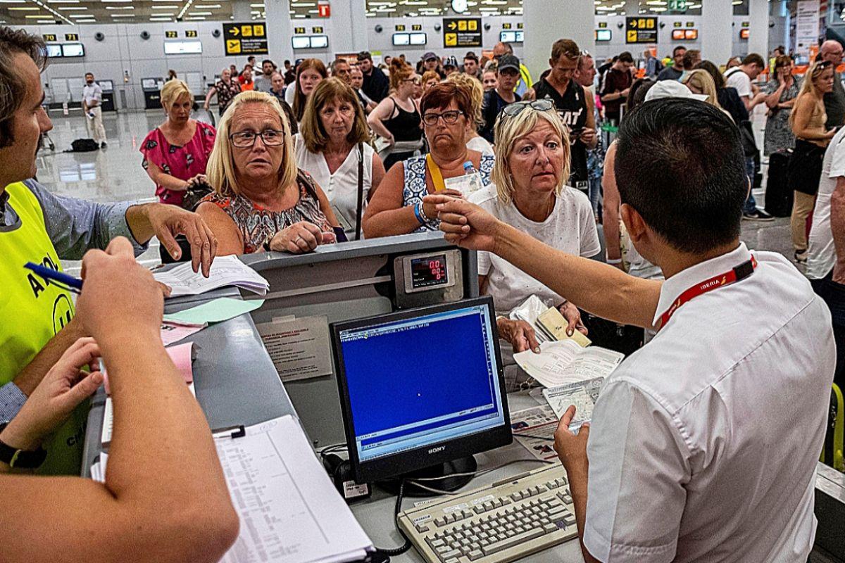 Turistas haciendo cola en uno de los mostradores de facturación del aeropuerto de Palma el pasado verano.