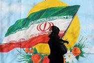 Una mujer iraní se protege con una mascarilla mientras pasea en Teheran.