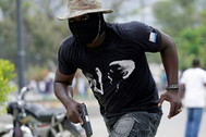 A protester carrying a gun runs during a shooting at a protest called by members of the police, in Port-au-Prince
