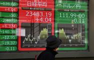 Un ciudadano camina ante pantallas que reflejan la cotización bursátil en Tokio.