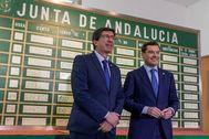 El presidente, Juan Manuel Moreno, y el vicepresidente, Juan Marín, posan delante de la tabla en la que se apuntaron los resultados del referéndum en 1980.