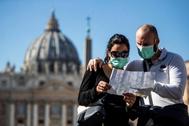 Dos turistas consultan un plano junto al Vaticano.