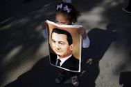Una niña muestra una imagen de Mubarak en el exterior del hospital en el que se encontraba hospitalizado en las afueras de El Cairo, en 2015.