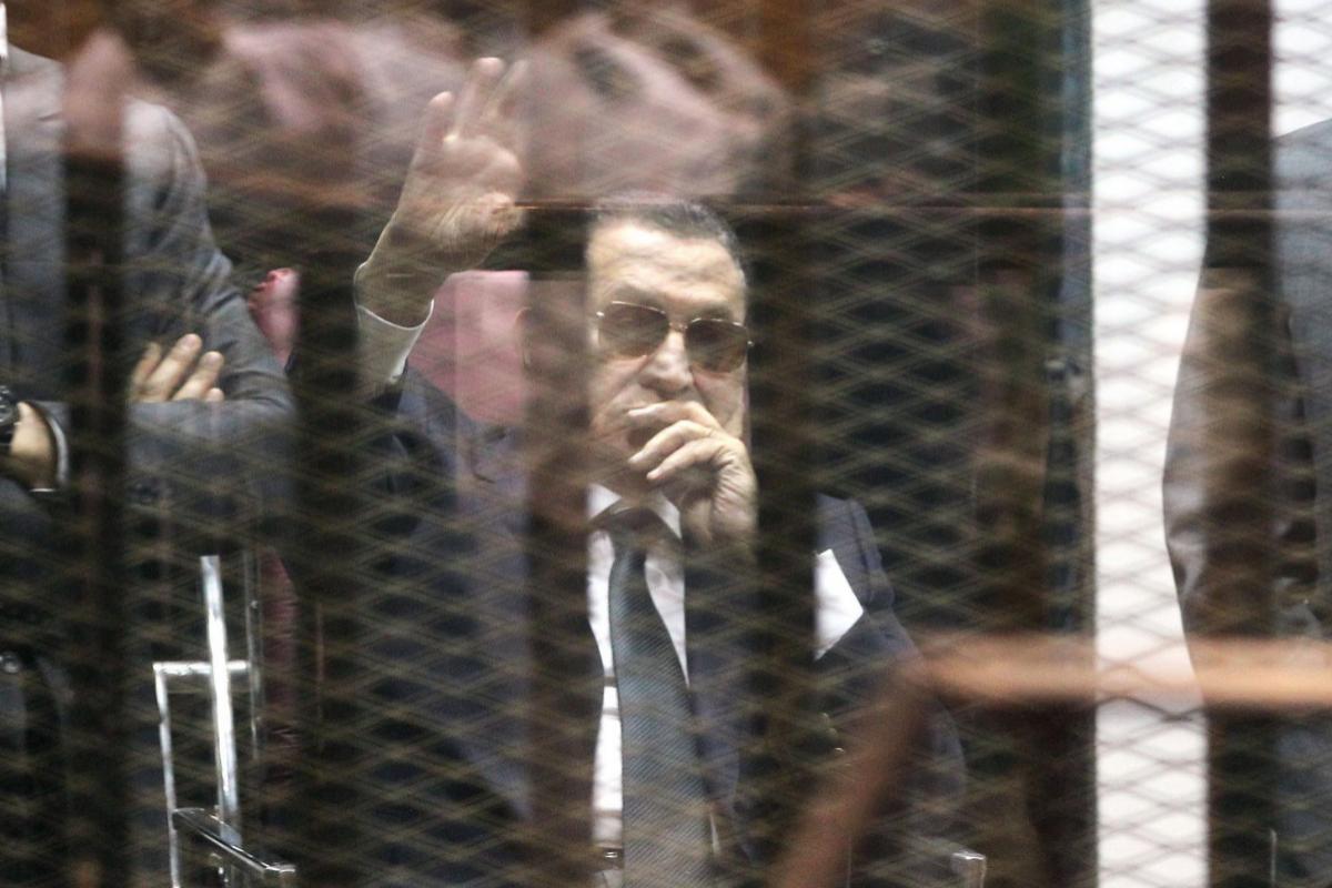Hosni Mubarak saluda desde la celda de los acusados en un juicio en 2015.