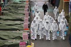 Empleados de un mercado en Daegu desinfectan los puestos de venta.