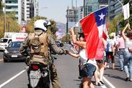 Una mujer saluda a un carabinero durante una marcha en rechazo a una nueva Constitución chilena.