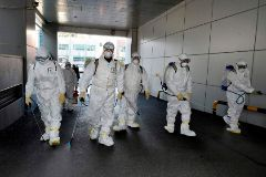 """This handout picture taken on February 19, 2020 by Daegu Metropolitan City Namgu shows South Korean health officials wearing protective suit and spraying disinfectant in front of the Daegu branch of the lt;HIT gt;Shincheonji lt;/HIT gt; Church of Jesus in the southeastern city of Daegu as about 40 new cases of the COVID-19 coronavirus confirmed after they attended same church services. - A cluster of novel coronavirus infections centred on a cult church in the South Korean city of Daegu leaped to 39 cases February 20, as the country's total spiked for the second successive day. (Photo by Handout / Daegu Metropolitan City Namgu / AFP) / RESTRICTED TO EDITORIAL USE - MANDATORY CREDIT """"AFP PHOTO / Daegu Metropolitan City Namgu"""" - NO MARKETING NO ADVERTISING CAMPAIGNS - DISTRIBUTED AS A SERVICE TO CLIENTS"""