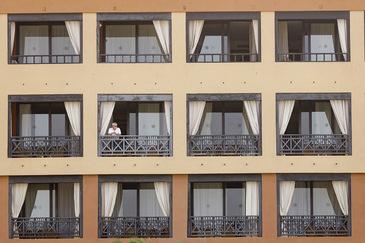 Un huésped se asoma a un balcón del hotel tinerfeño donde se hospedaba un médico italiano que ha dado positivo en Covid-19.