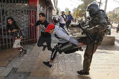 Un manifestante es golpeado por un policía durante protestas en Chile.